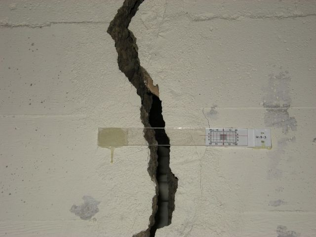 Wall crack with fissurometer, to gauge the relative movement of the two parts of the building. Photo: Joe Mabel